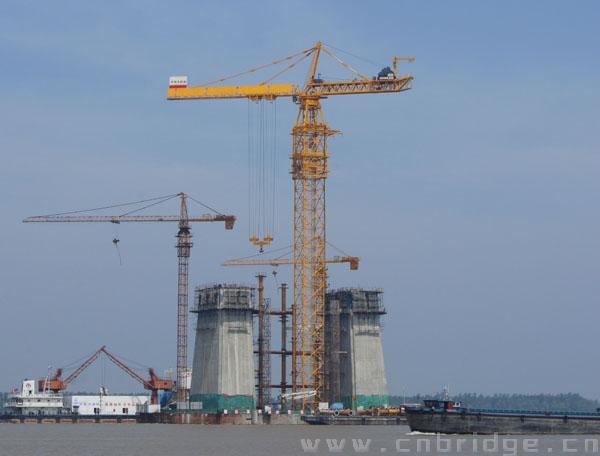 大桥局项目经理刘俊是技术出身,清瘦的他谈起大桥建设过程中攻克的一个又一个难关,如数家珍。刘总告诉记者,在建的中塔高175.8米,钢塔柱拼装节段42个,最大吊装重量达580吨,单节段吊装重180吨,吊装精度要求塔柱垂直误差不超过1/4000,而且中塔建设中采用的钢砼叠合的创新结构,其上塔柱钢塔施工技术新颖、工序复杂、施工难度极大,施工控制非常困难。为了攻克超大体积、超重钢塔吊装的技术难题,中铁大桥局集团出资与中联重科联手研制出了D—5200塔吊,D—5200塔吊的吊高可达210