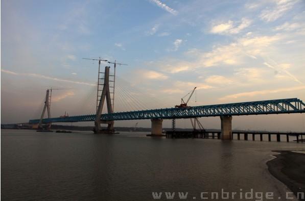 """12月19日,随着安庆长江大桥边跨合龙段最后一根杆件顺利对接,世界最大跨度的四线铁路斜拉桥——宁安铁路安庆长江大桥全桥精确合龙。   安庆长江大桥是南京至安庆城际铁路的重要组成部分和控制性工程。大桥全长2996.8米。主桥为双塔三桁三索面六跨连续非对称钢桁梁斜拉桥,长1363米。安庆长江大桥具有""""深水、大跨、高速、重载""""的特点,是宁安城际铁路的标志性工程,技术含量高、施工难度大。建造这样一座世界级大桥,需要浇筑混凝土近40万立方米,钢材11余万吨。"""
