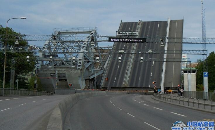 行走在瑞典首都斯德哥尔摩Stockholm,路人竟然巧遇了并列的一座滚轮型铁路开启桥和一座竖旋型公路开启桥Danviksbron bridge同时开启的壮观场面。开启桥Movable Bridge亦称活动桥、开合桥,是为通航需要,桥身能以竖旋、平旋、提升等方式开合的桥梁。适用于桥上交通不甚繁忙、同时桥下须通行高大船只的河道或港口,优点是墩台较低因而能减少两岸引桥和路堤的工程量,缺点是需要增加机械维修费用。开启桥的活动方式包括:一类是桥跨结构和桥面在桥轴线所在竖直平面内移位(包括水平移位和转动移位),如